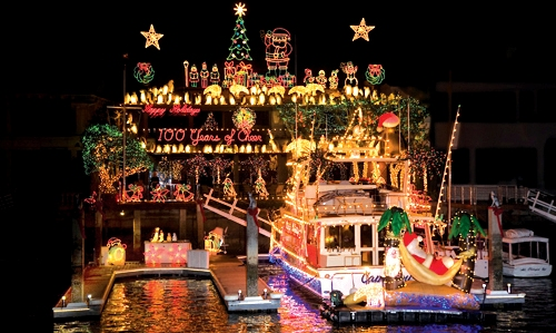 A boat lit up and decorated sits in the Newport dock